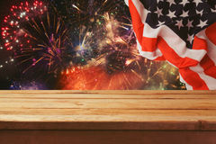 4th of July background. Wooden table over fireworks and USA flag. Independence day celebration. Event Stock Photography