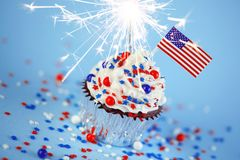 4th of July cupcake with flag, sprinkles, sparkler Royalty Free Stock Images