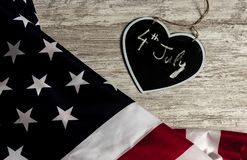 4th July date in black heart and united states flag. Overhead picture of united states flag and black heart including the date 4th July inside, all over wood stock photos