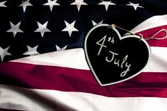 4th July date in black heart, on united states flag. Overhead picture of black heart including the text of the date 4th July inside, on united states flag royalty free stock photography