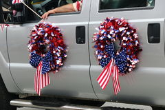 4th of July flag wreaths. Wreaths decorated with American flags on the doors of a vehicle at the Independence Day parade, Monterey, CA Royalty Free Stock Images