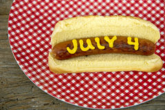 4th of July holiday hot dog. Mustard on hot dog with bun for 4th of July on red and white gingham plate Stock Photo