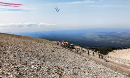 14th July Over Le Tour de France. Mont Ventoux, France- July 14 2013: Planes formation fly above the Mount Ventoux while people rise up the last kilometer mark Stock Photography