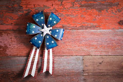 4th July patriotic badge on rustic wood. 4th July patriotic badge in the form of a circular rosette with blue stars and a ribbon with the red and white stripes Royalty Free Stock Photo