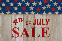 4th of July sale message. 4th of July Sale text with USA red and blue stars burlap ribbon on weathered wood Stock Photo