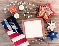 4th of July Table Setting with Flag Napkin, silverware, decorations and a blank white card with space for copy, text or your words