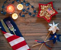 4th of July Table Setting with Rustic Wood Background providing copy space, and red white and blue decorations.  It`s a horizonta. L with moody lighting and a royalty free stock images