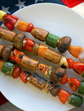 4th of July vegan bbq. Vegetarian kebab with mushrooms, zucchini, tomatoes, peppers, garlic, and vegan sausage on skewers at a 4th of July barbecue. A healthy royalty free stock photo