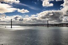 25th Kwietnia most w Lisbon pod chmurnym niebem Zdjęcia Royalty Free