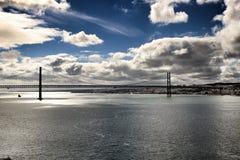 25th Kwietnia most w Lisbon pod chmurnym niebem Zdjęcia Stock