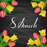 8th March Womens Day on black chalkboard background with tulips. International Womens Day on black chalkboard background with tulips. Golden lettering 8th March Stock Image