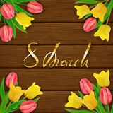 8th March Womens Day on brown wooden background with tulips. International Womens Day on brown wooden background with tulips. Golden lettering 8th March Stock Image