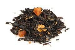 Thé noir avec des fruits secs et des pétales d'isolement sur le fond blanc Image stock