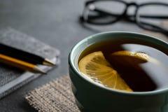 Th? noir avec des tranches de citron sur une serviette de toile de jute avec le stylo de bloc-notes, un crayon et des verres photographie stock libre de droits