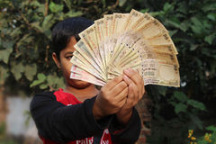 9th November, 2016, India- A unidentified boy took some Indian currency in the air. Now these currencies are invalid. Waiting for rebirth royalty free stock image