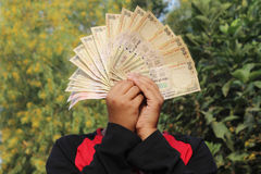 9th November, 2016, India- A unidentified boy took some Indian currency in the air. Royalty Free Stock Photo