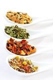 Thé sec assorti de santé de fines herbes dans des cuillères Photographie stock