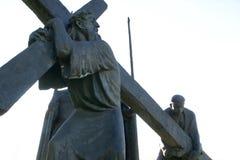 5th stationer av korset, Simon av Cyrene bär korset Arkivfoto