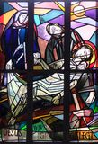 14th Stations of the Cross, Jesus is laid in the tomb and covered in incense. Stained glass window in Saint Lawrence church in Kleinostheim, Germany Stock Photos