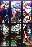 14th Stations of the Cross, Jesus is laid in the tomb and covered in incense. Stained glass window in Saint Lawrence church in Kleinostheim, Germany Stock Images