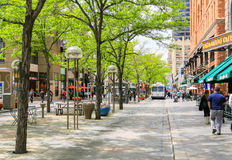 The 16th Street Mall. Denver, USA - May 25, 2016: The 16th street mall in downtown with shops and cafes and green trees in the middle of the street. People are Stock Photography