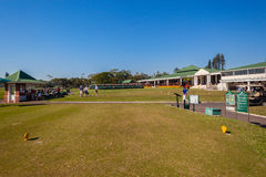 10th Tee Box Golf Club. Photo image standing on 10th hole tee box with distant carts putting green and club house at Mount Edgecombe golf club in Durban South Royalty Free Stock Photo