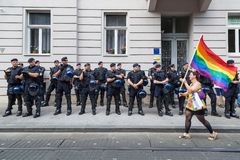 15th Zagreb pride. LGBTIQ activist passing by police cordon holding rainbow flag. ZAGREB, CROATIA - JUNE 11, 2016: 15th Zagreb pride. LGBTIQ activist passing by royalty free stock photo