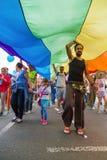 15th Zagreb pride. LGBTIQ activist under big rainbow flag. ZAGREB, CROATIA - JUNE 11, 2016: 15th Zagreb pride. LGBTIQ activist under big rainbow flag royalty free stock photo