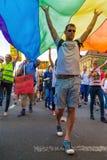 15th Zagreb pride. LGBTIQ activist under big rainbow flag. ZAGREB, CROATIA - JUNE 11, 2016: 15th Zagreb pride. LGBTIQ activist under big rainbow flag stock photo