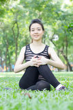 Thai adult beautiful girl doing yoga exercises in the park Stock Photo