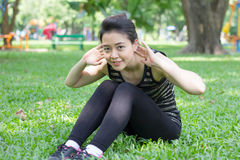 Thai adult beautiful girl doing yoga exercises in the park Royalty Free Stock Photo