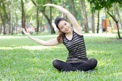 Thai adult beautiful girl doing yoga exercises in the park Royalty Free Stock Images