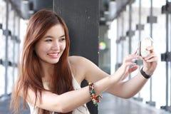 Thai adult beautiful girl using her smart phone Selfie. Stock Photo