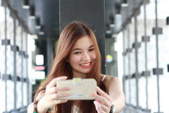 Thai adult beautiful girl using her smart phone Selfie. Stock Photos