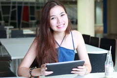 Thai adult beautiful girl using her tablet and smile in university. Stock Photography