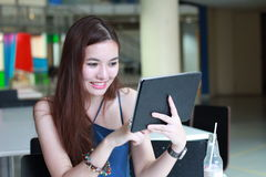 Thai adult beautiful girl using her tablet and smile in university. Royalty Free Stock Images