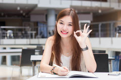 Thai adult beautiful girl write a book and smile in university. Stock Photo
