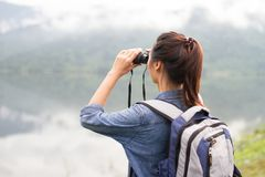 Thai adventure girl wathcing with binoculars. On the lakeside Royalty Free Stock Images