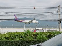Thai Airway airplane is landing at Chiang Mai International Airport, Chiang Mai, Thailand, flying low above the street with traffi royalty free stock photography