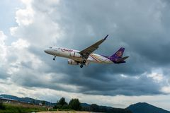 Thai Airways airbus A320 is landing at Phuket Airport, photograph from checkpoint of Thailand. Phuket, Thailand - November 21, 2017: Thai Airways airbus A320 is Stock Photography