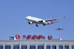 Thai Airways Airbus 330-343X skims over a building of China Aviation Oil Corporation, Beijing, China Stock Photography