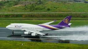 Thai Airways entfernen sich an Phuket-Flughafen auf nasser Rollbahn mit Spl Stockbild