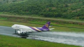 Thai Airways entfernen sich an Phuket-Flughafen auf nasser Rollbahn mit Spl Lizenzfreie Stockfotografie