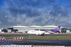 Thai Airways hyvlar att ta av med bakgrund för molnig himmel Royaltyfri Foto