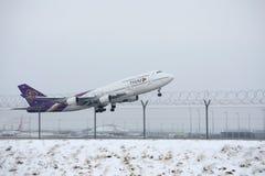 Thai Airways International Boeing 747-400 HS-TGB in München-Flughafen, Winter Stockbild
