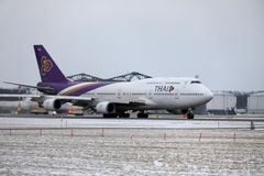 Thai Airways International Boeing 747-400 HS-TGG dans l'aéroport de Munich, hiver Photographie stock libre de droits