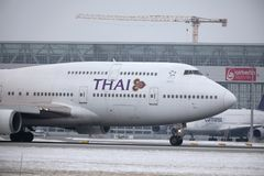 Thai Airways International Boeing 747-400 HS-TGG i den Munich flygplatsen, vinter Royaltyfri Bild