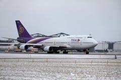 Thai Airways International Boeing 747-400 HS-TGG i den Munich flygplatsen, vinter Royaltyfri Fotografi