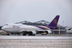 Thai Airways International Boeing 747-400 HS-TGG in München-Flughafen, Winter Lizenzfreie Stockfotografie