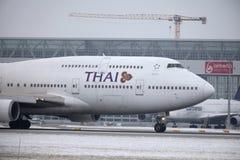 Thai Airways International Boeing 747-400 HS-TGG in München-Flughafen, Winter Lizenzfreies Stockbild